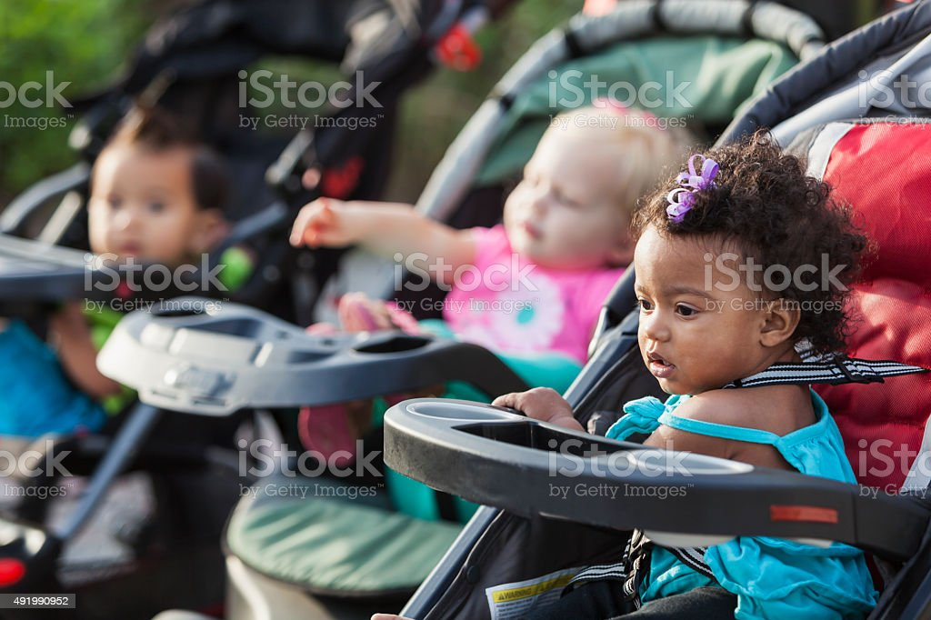 Three multi-racial babies in baby strollers stock photo