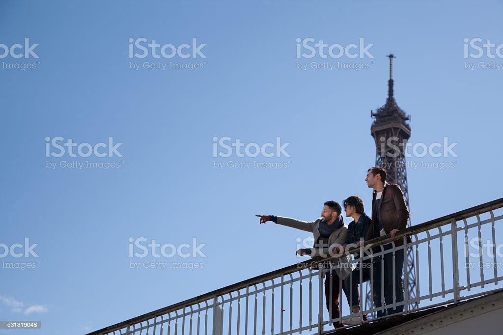 three multiracial friends check views  at Eiffel Tower Paris stock photo