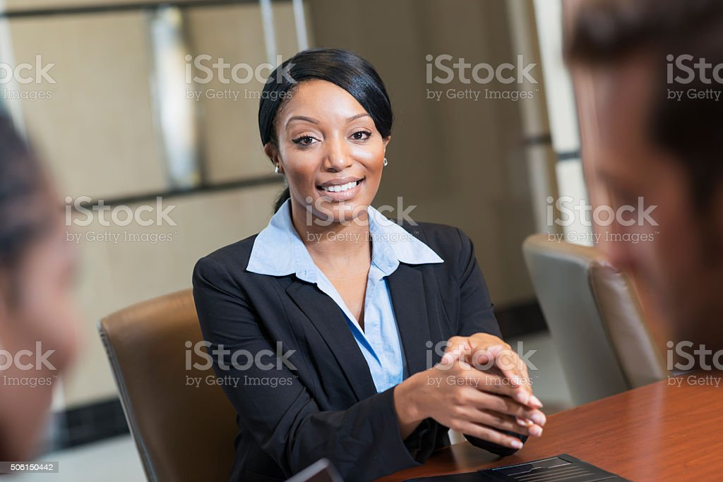 Three multi-racial office workers in boardroom stock photo