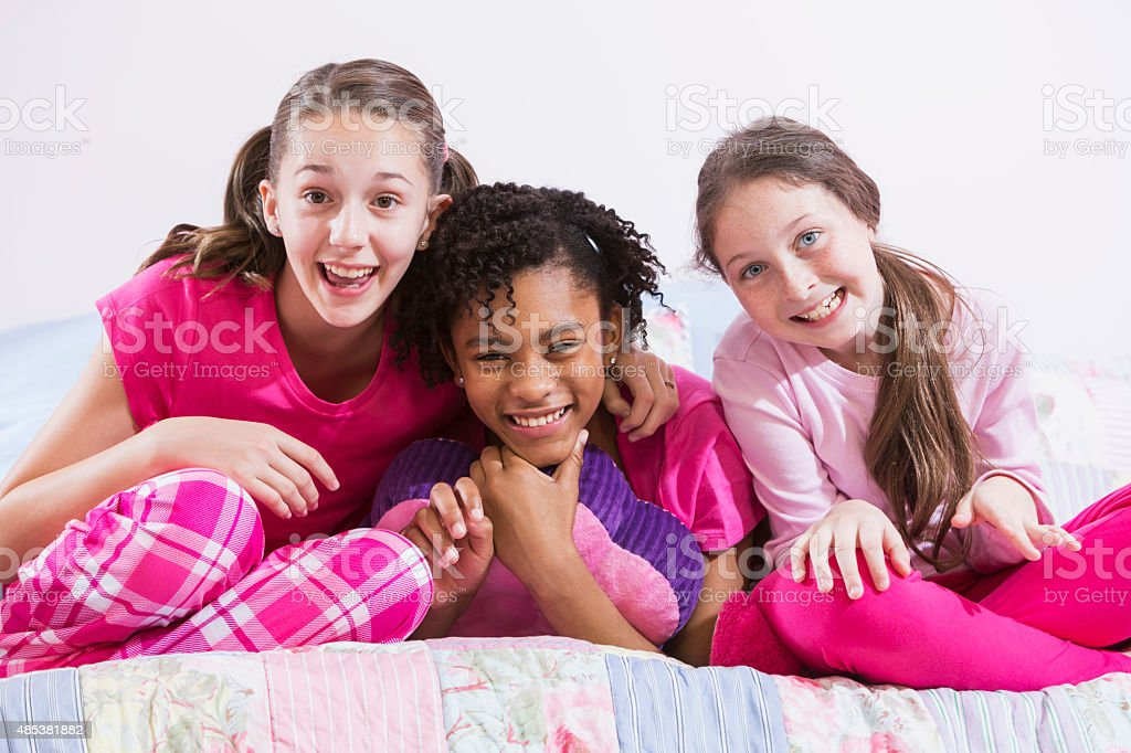 Three multiracial preteen girls at slumber party stock photo