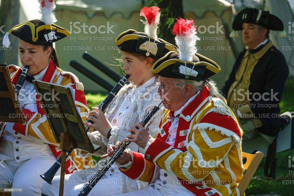 Three musicians play an 18th-century score in a war reenactment stock photo