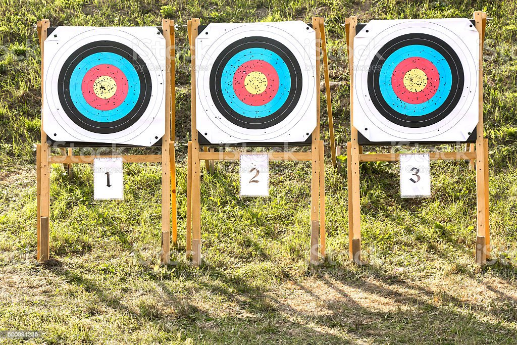 Three of paper archery targets in wooden stands stock photo