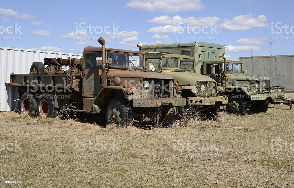 three old army vehicles parked in a grass field royalty-free stock photo