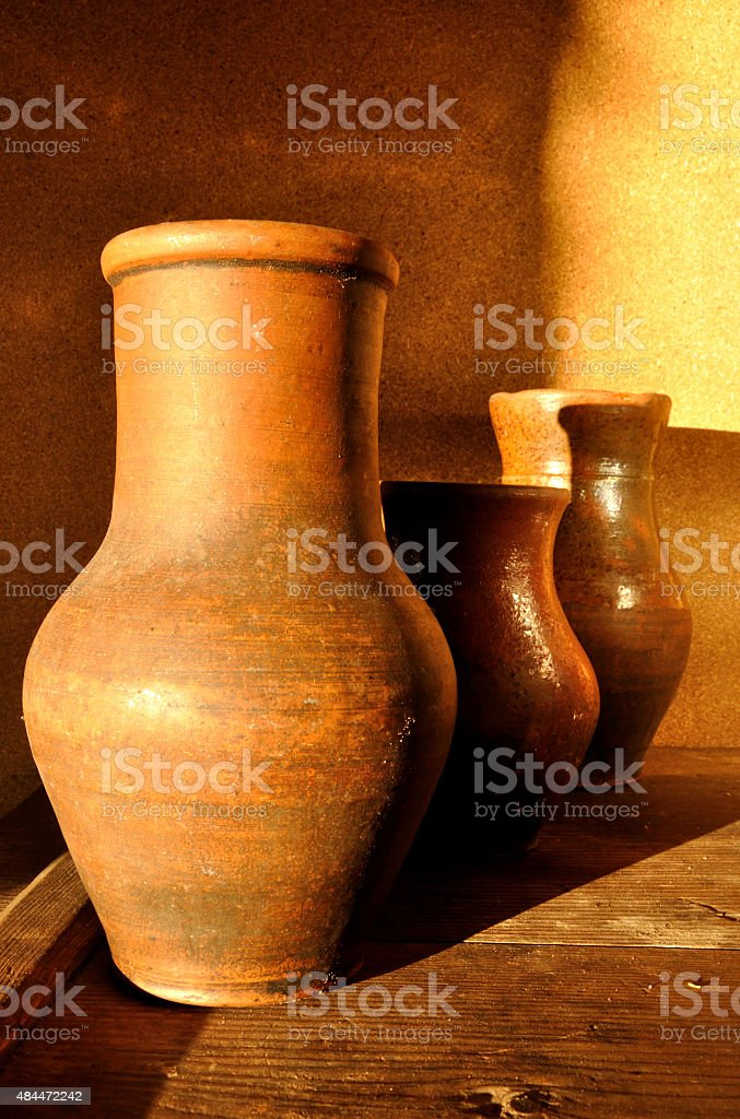 Three old ceramic pitchers in a storeroom stock photo