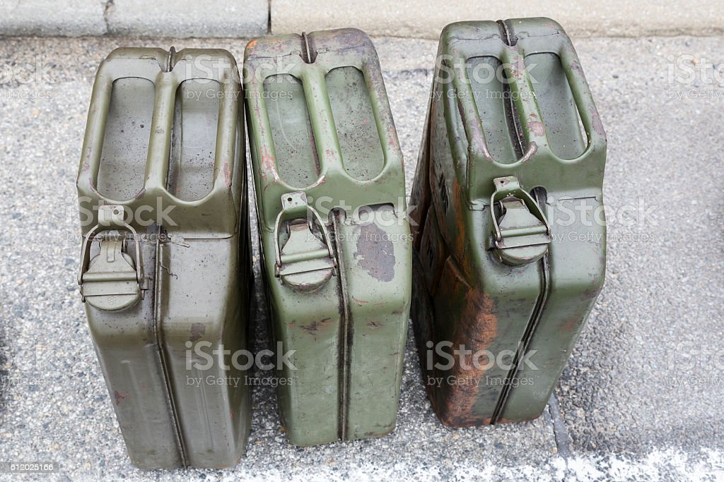 three Old jerry cans with gasoline on the road stock photo