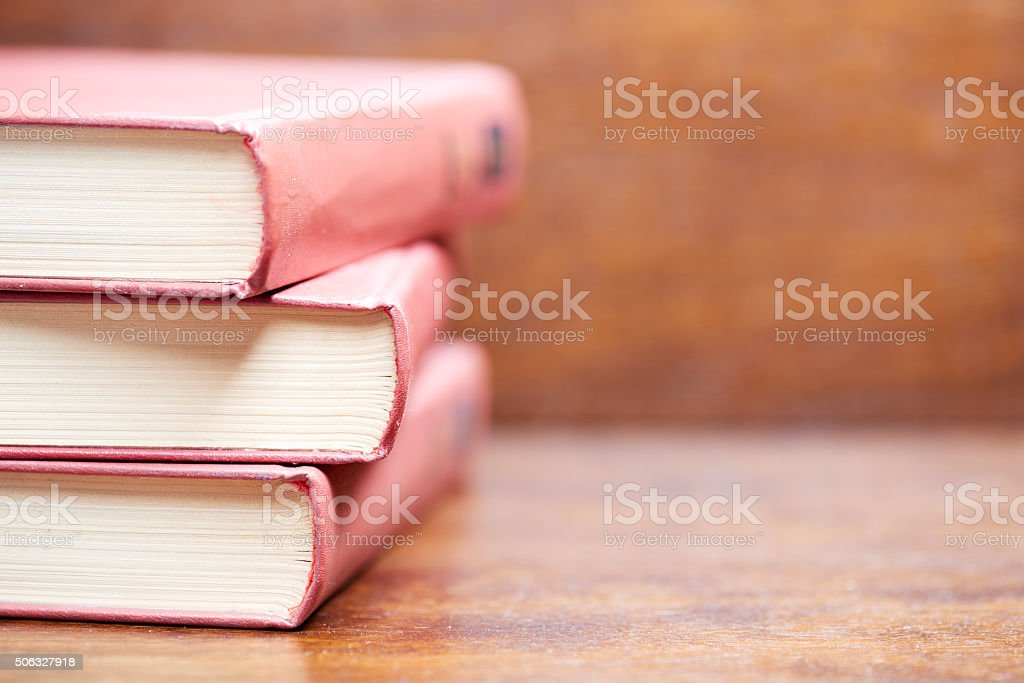 Three old red books on the table stock photo