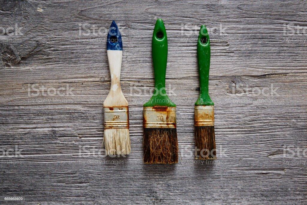 three old rusty paintbrushes on raw wood stock photo