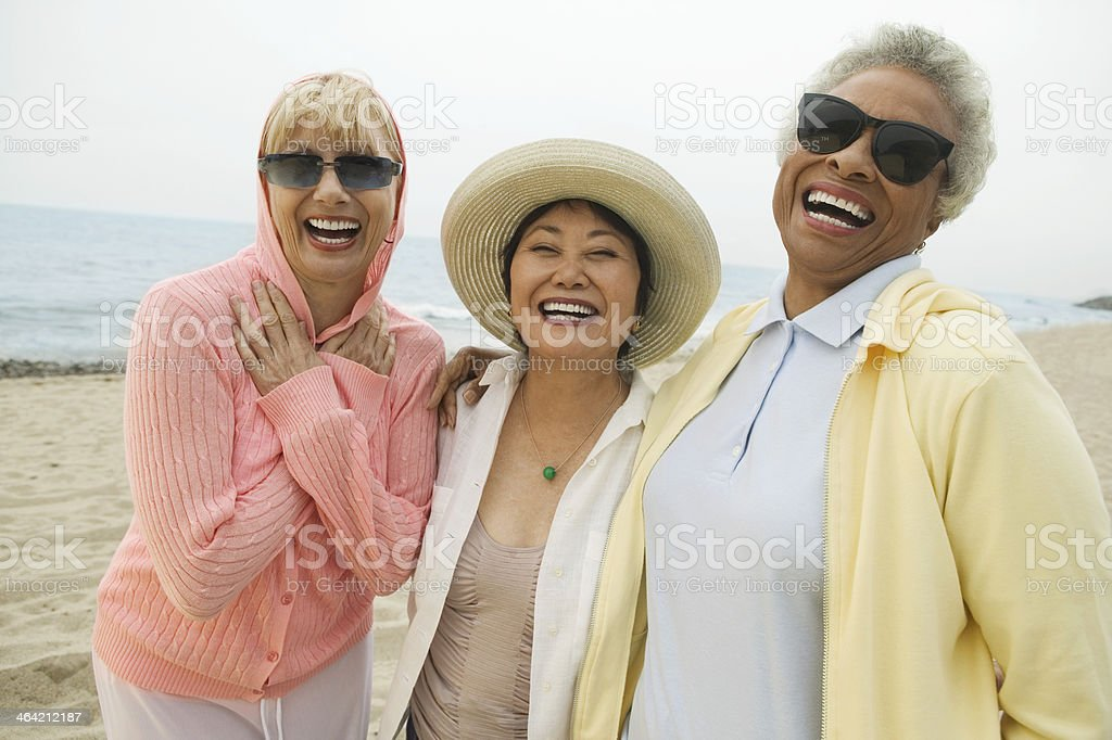Three older woman laugh while on the beach stock photo