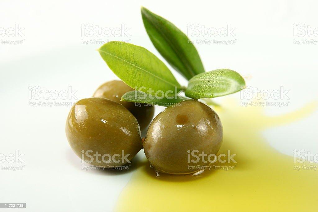 three olives on olive oil stock photo