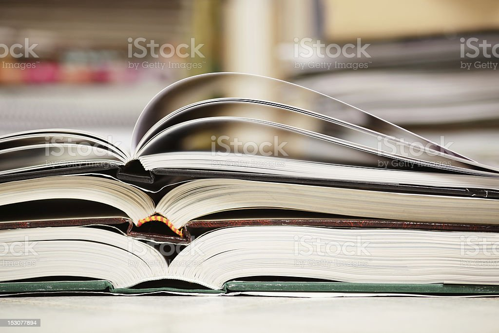 Three open books stacked on top of one another stock photo