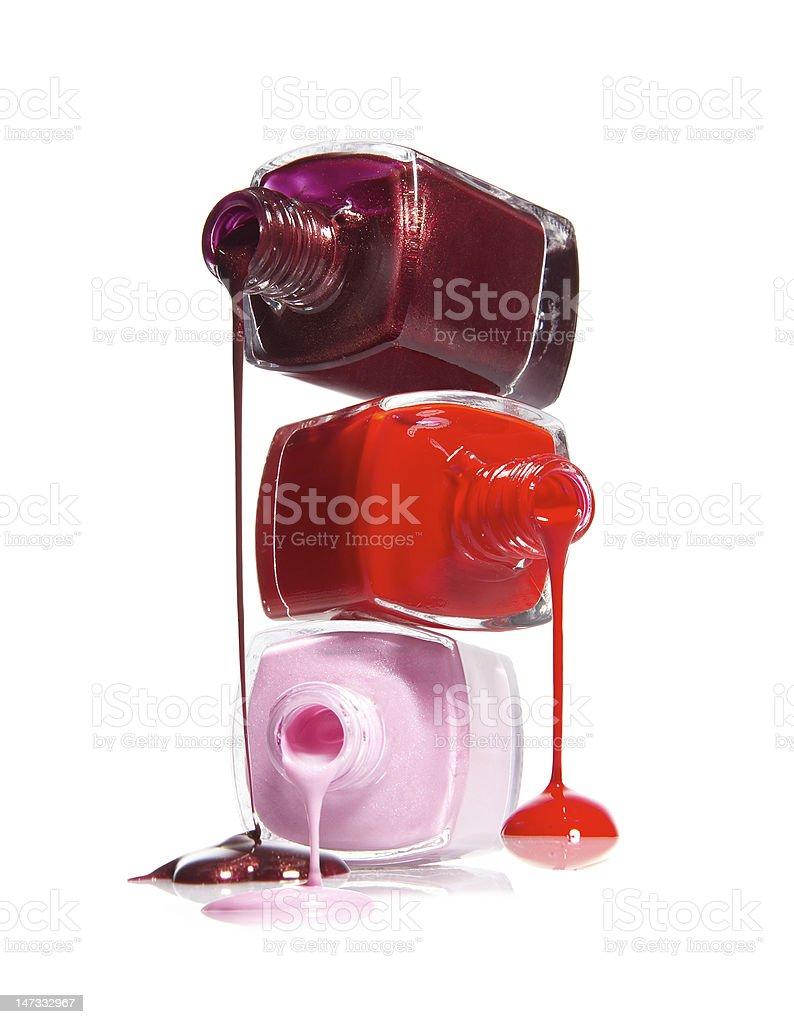 Three opened reddish nail polish jars stacked and spilling royalty-free stock photo