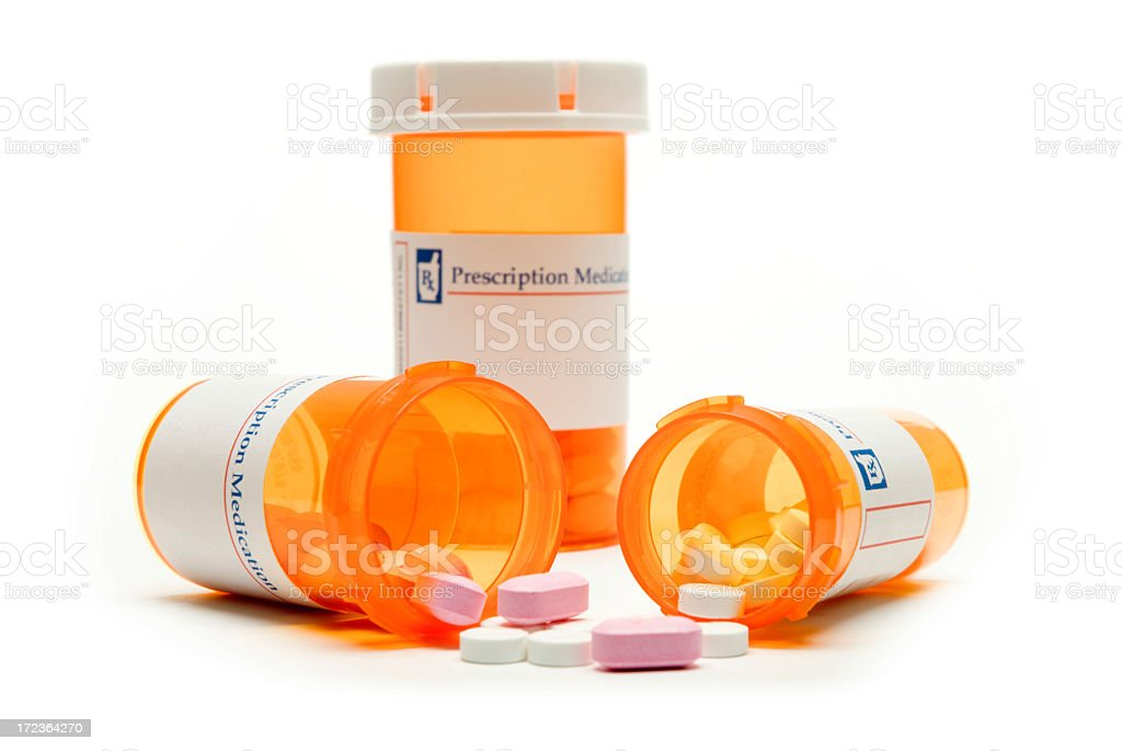 Three orange pills containers with two of them fallen down royalty-free stock photo