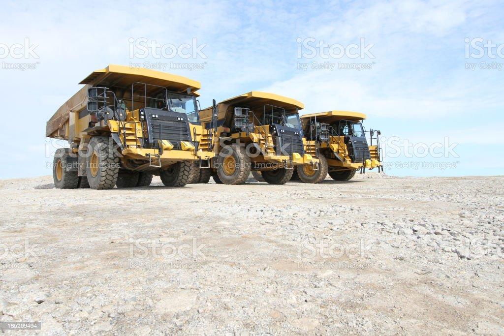 Three oversized dump trucks in a row royalty-free stock photo