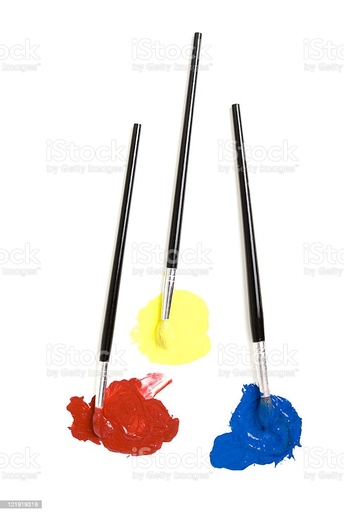 Three paintbrushes dipped in red, yellow and blue stock photo