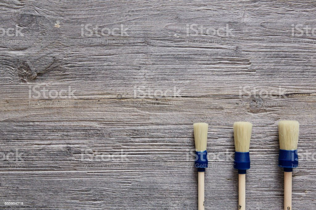 three paintbrushes organised on raw wooden table stock photo