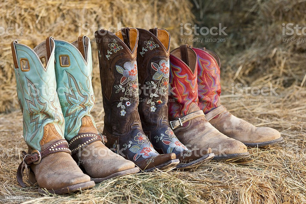 Three pair of cowboy boots sit on hay royalty-free stock photo