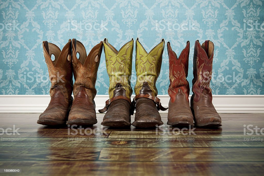 Three pairs of cowboy boots lined up against blue wallpaper stock photo