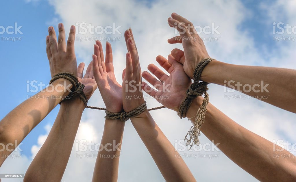 Three pairs of human hands tied up together stock photo