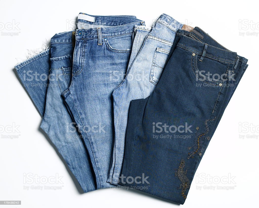 Three pairs of jeans folded on a white background stock photo