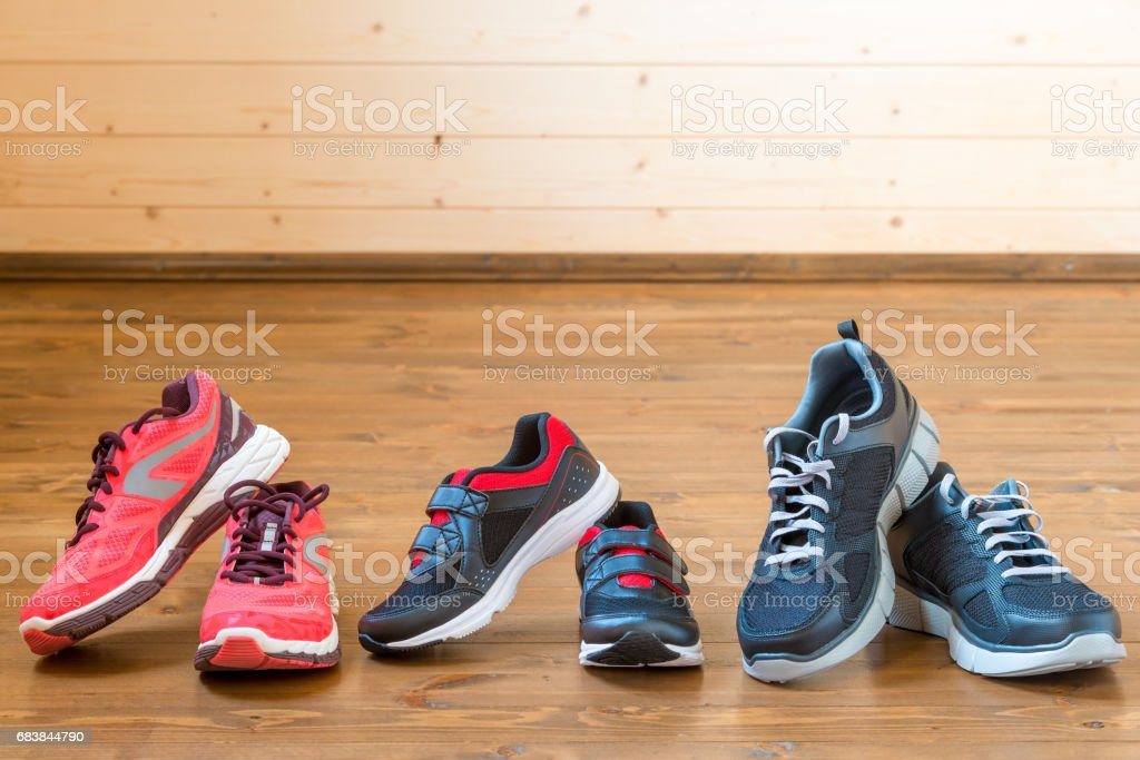 Three pairs of sports sneakers on a wooden floor close-up stock photo