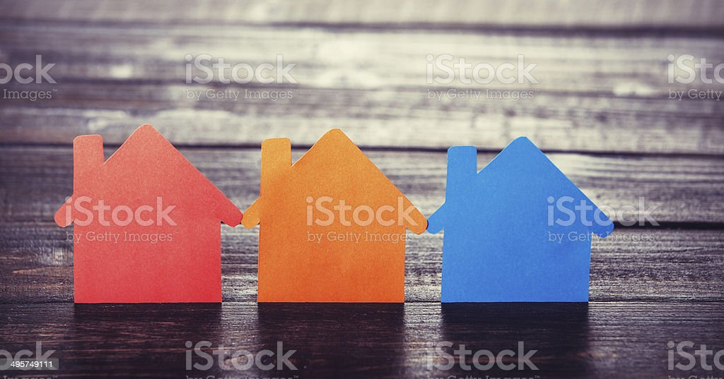 Three paper houses on wooden table. stock photo