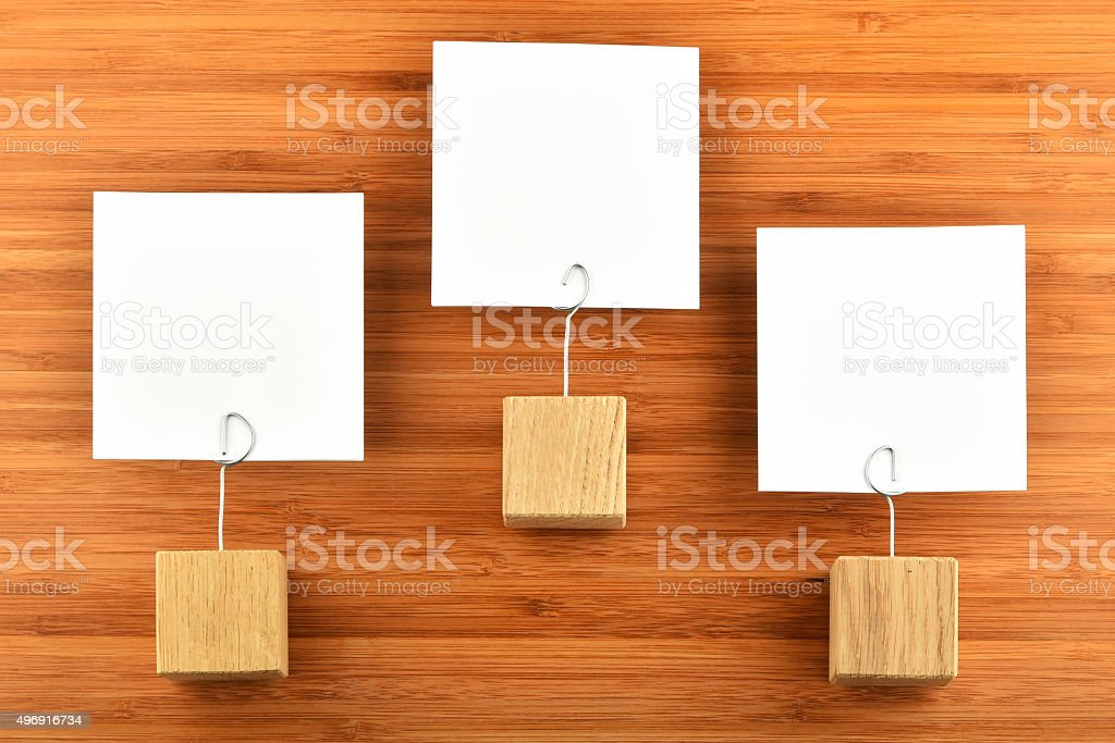 Three paper notes with holders isolated bamboo wooden background royalty-free stock photo
