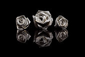 Three paper roses made from book pages isolated on black