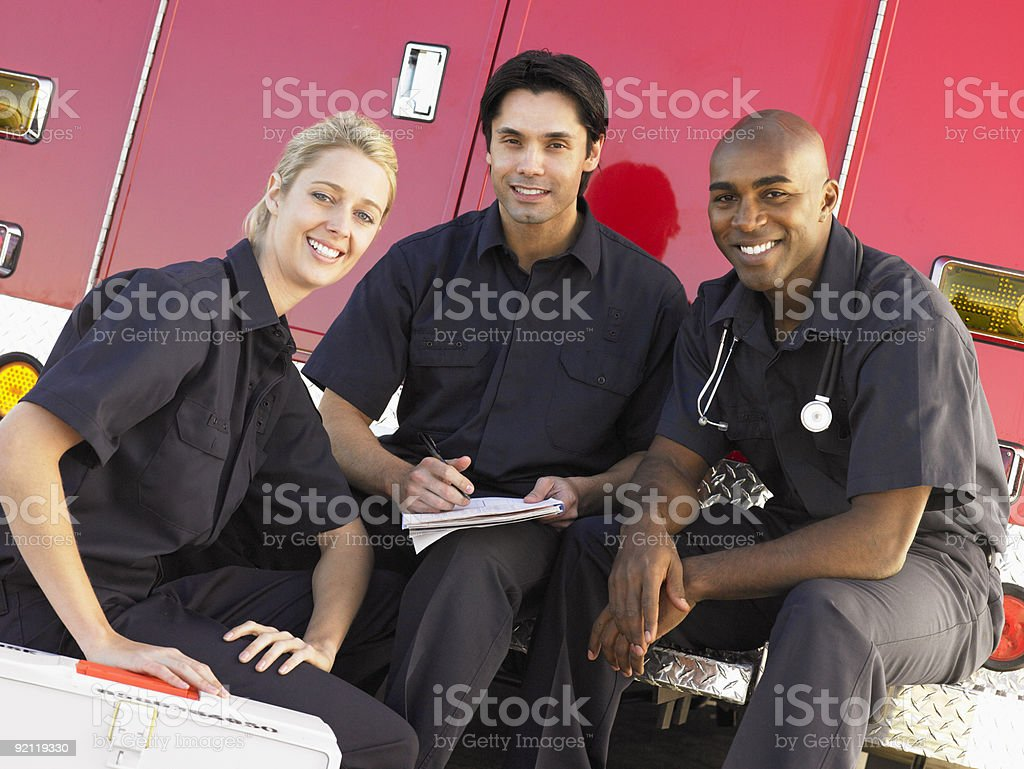 Three Paramedics By Their Ambulance stock photo