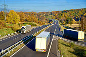 Three passing the trucks on a highway in autumn landscape