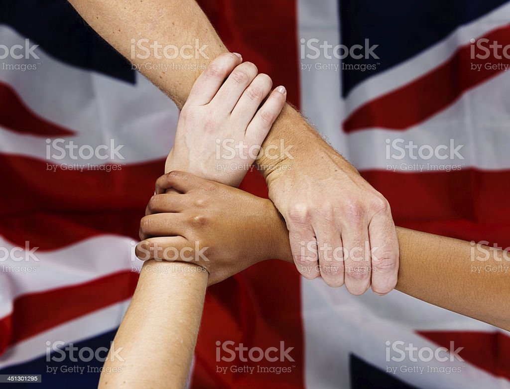 Three patriotic hands joined in front of Union Jack royalty-free stock photo