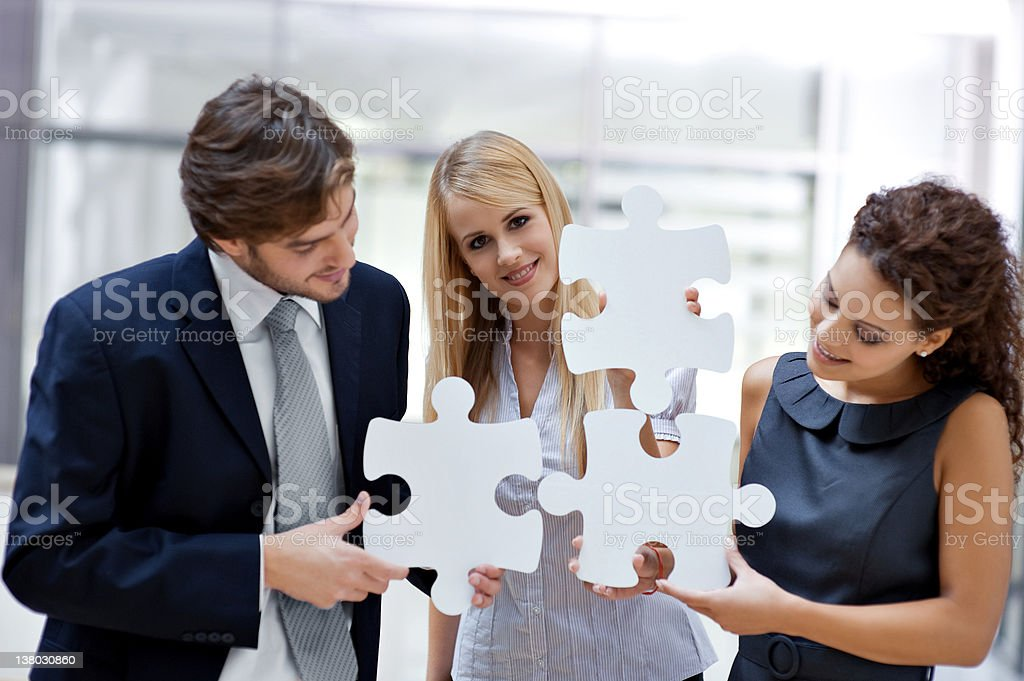 Three people are each holding a piece of jigsaw puzzle  royalty-free stock photo
