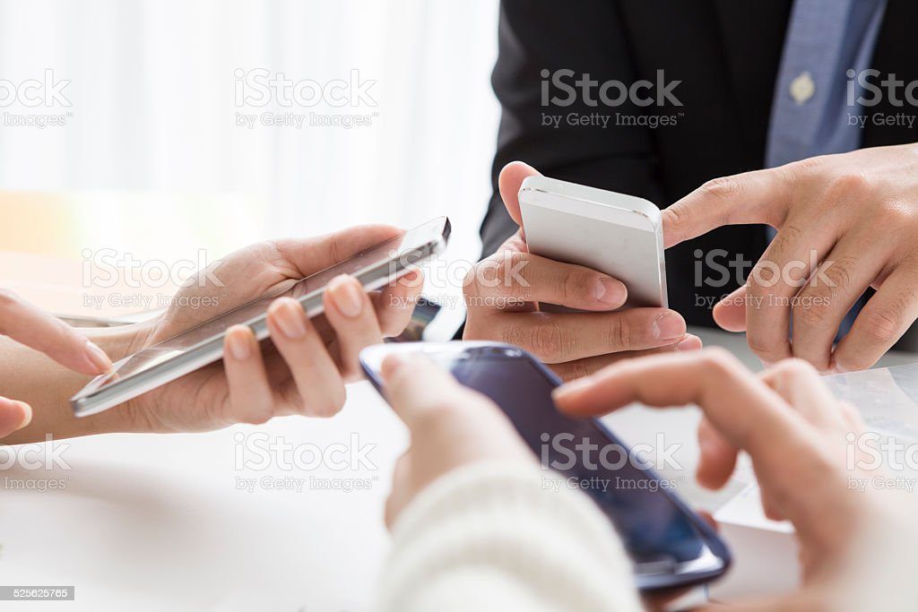 Three people are using mobile phone stock photo