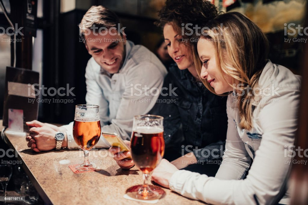 Three people hanging out in the pub stock photo