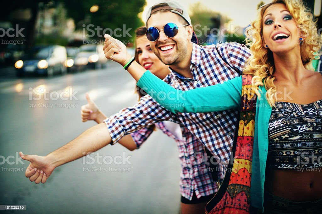 Three people hitchhiking in the city street. stock photo
