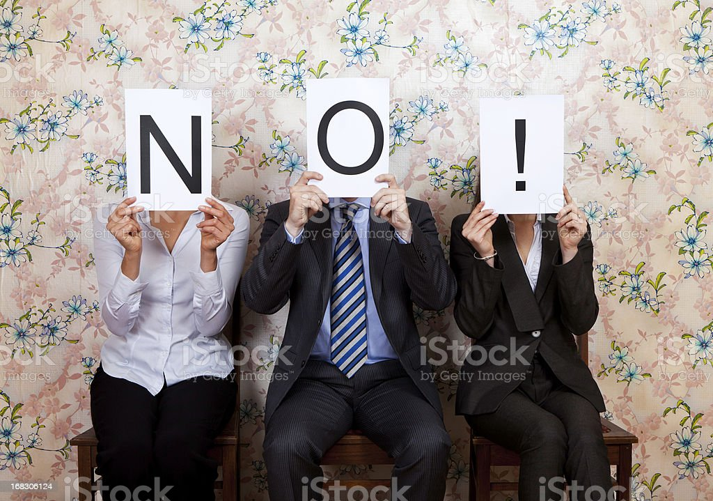 Three people holding the word NO! over their faces stock photo