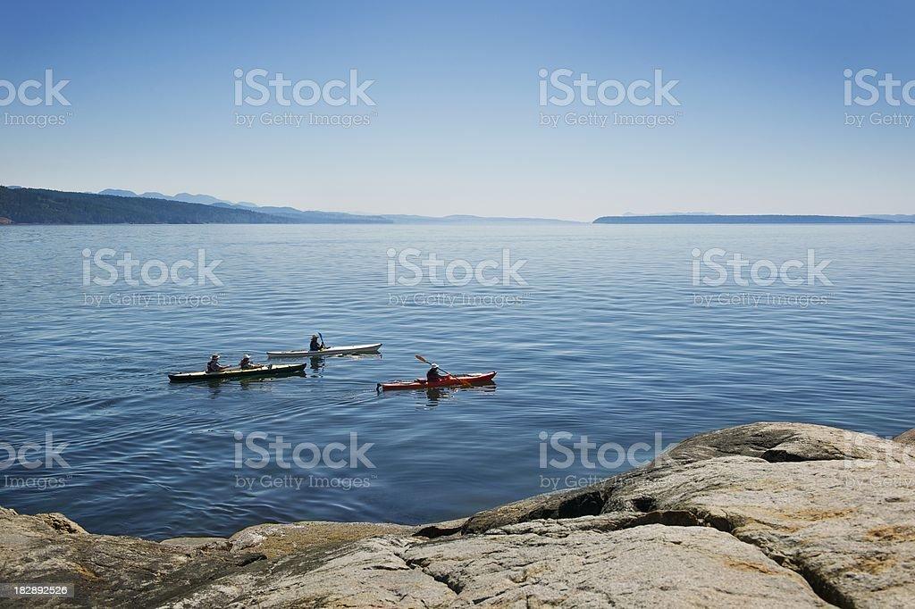 Three people kayaking on the coastline stock photo