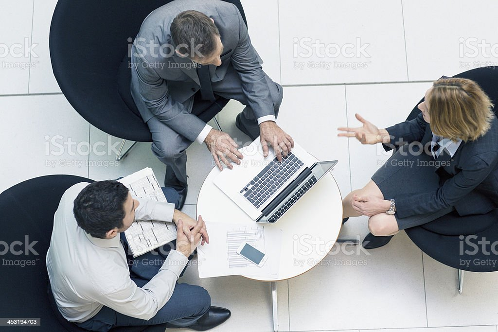 Three people meeting on small table in lobby stock photo