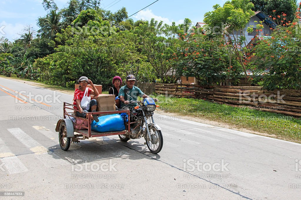 Three people on a tricycle in the Philippines stock photo