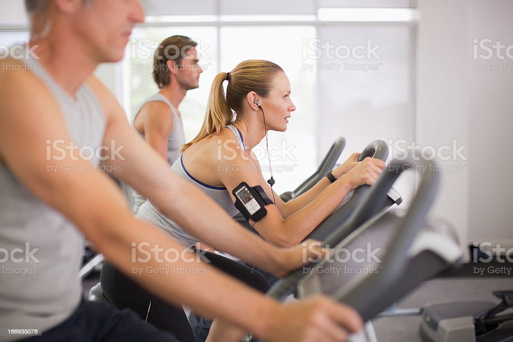 Three people on exercise bikes in gymnasium royalty-free stock photo