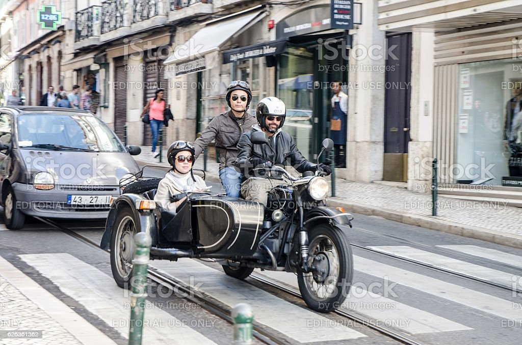 Three people passing by in a sidecar motorcycle stock photo