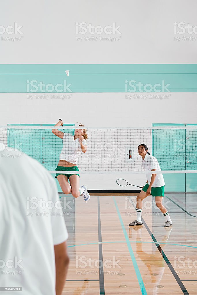 Three people playing badminton stock photo