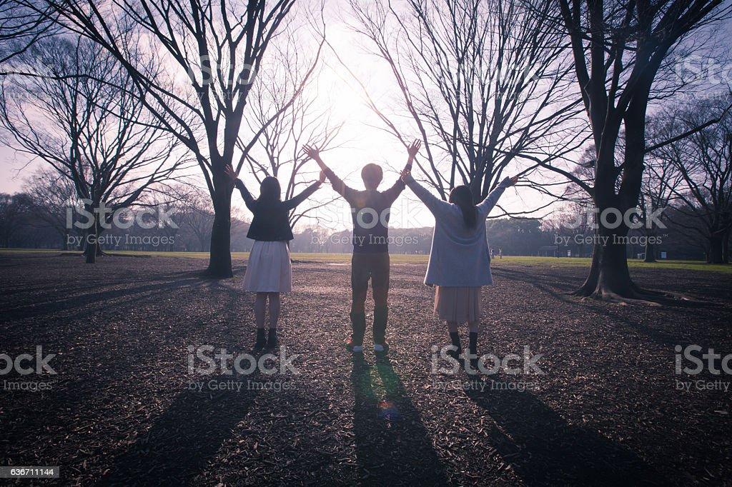 Three people raising hands against the sun stock photo