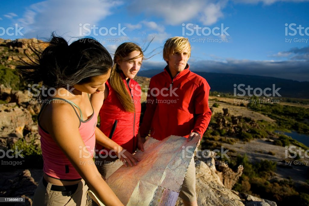 Three people reading a map royalty-free stock photo
