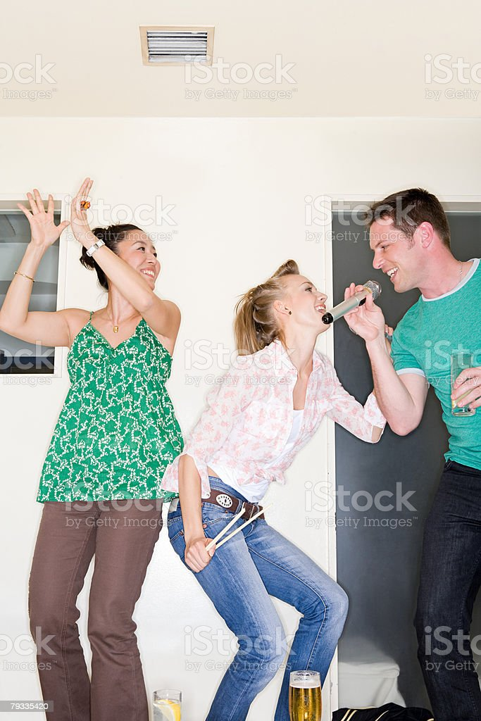 Three people singing karaoke royalty-free stock photo