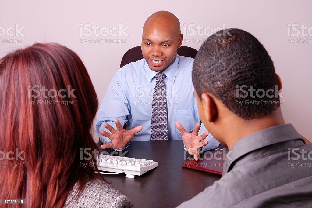 Three people sitting at a business desk, talking  royalty-free stock photo