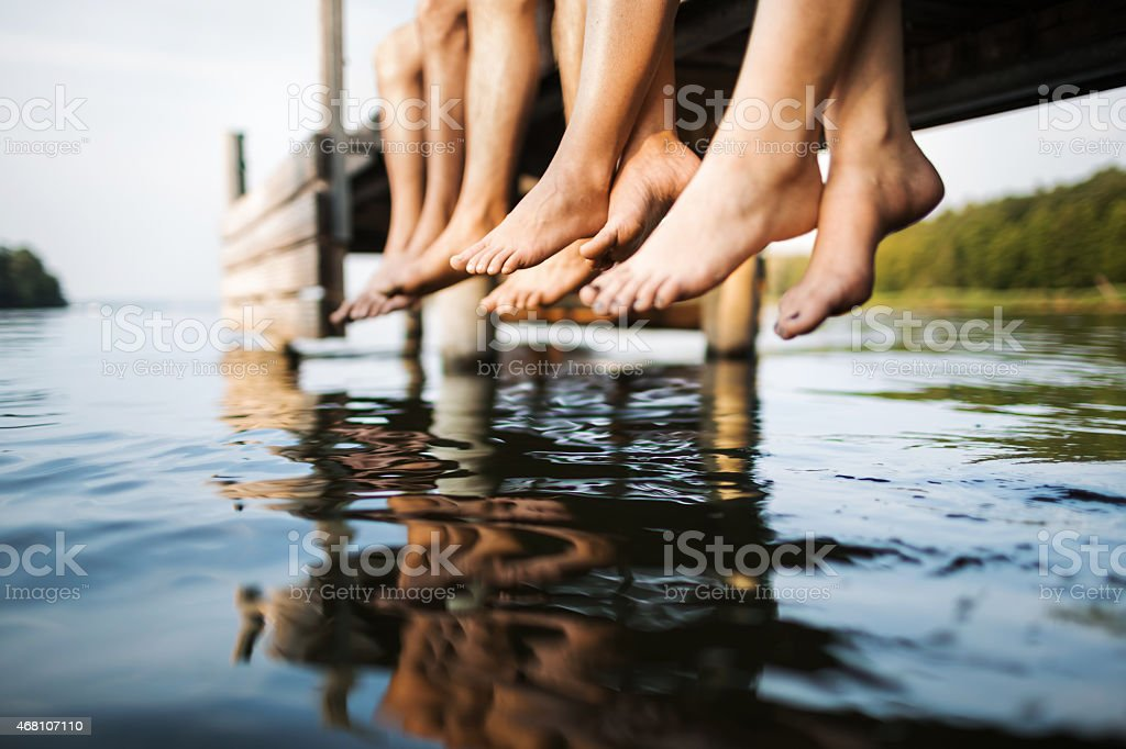 three people sitting on a jetty stock photo