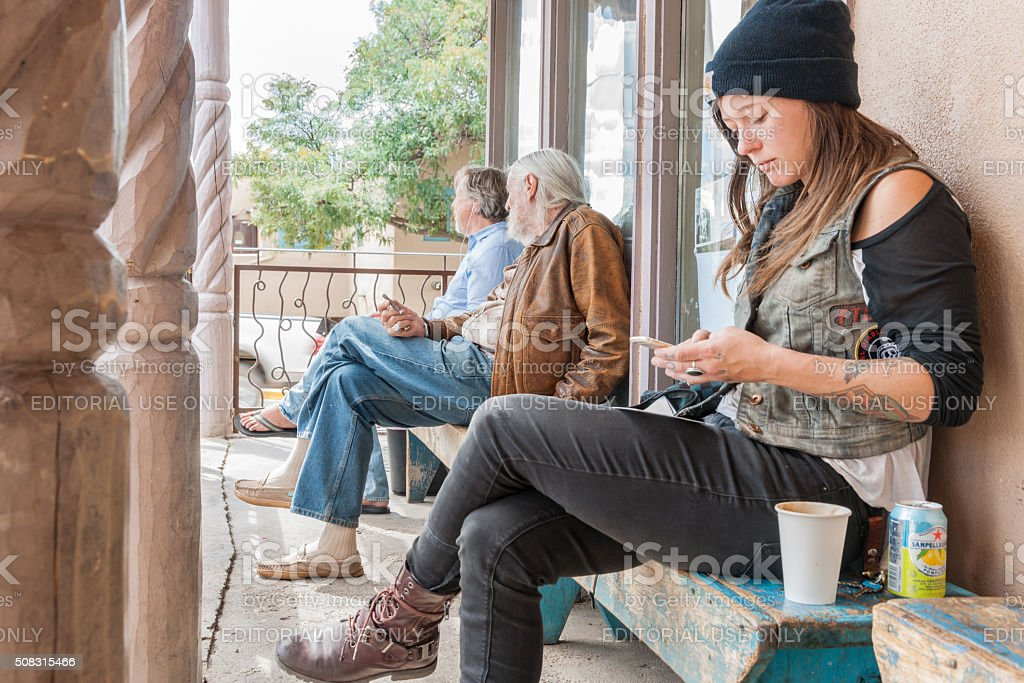 Three people sitting outside a cafe. stock photo
