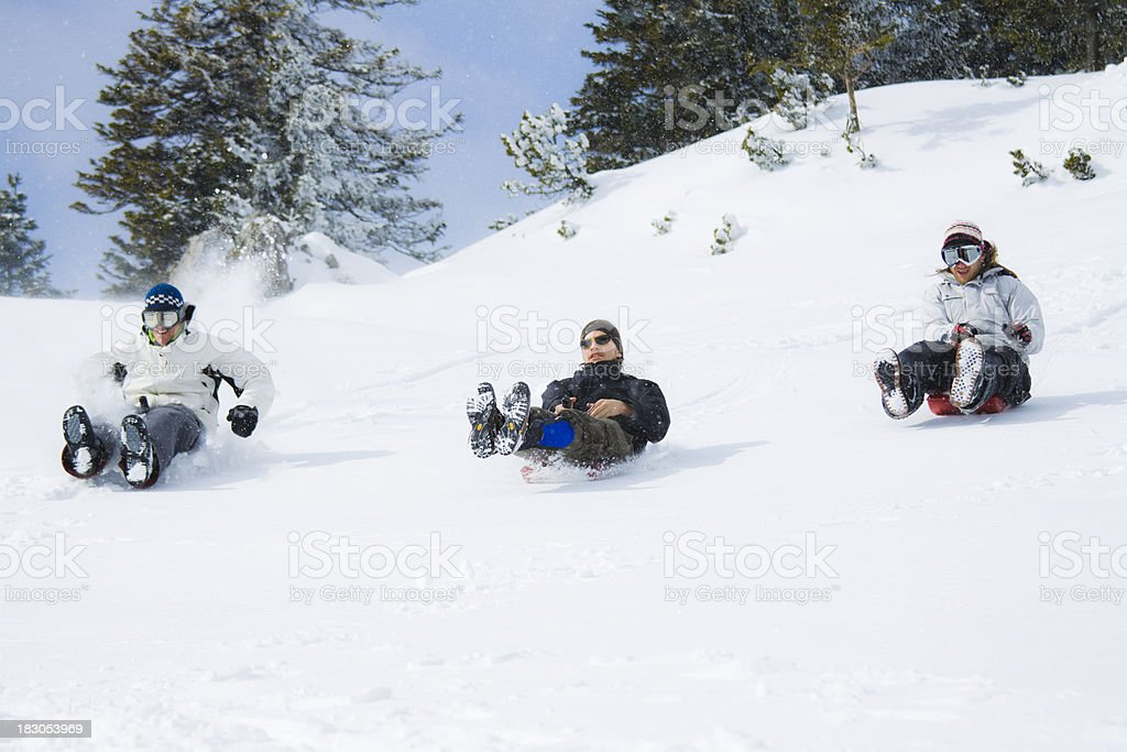 Three people sledding down a snowy hill in the winter royalty-free stock photo