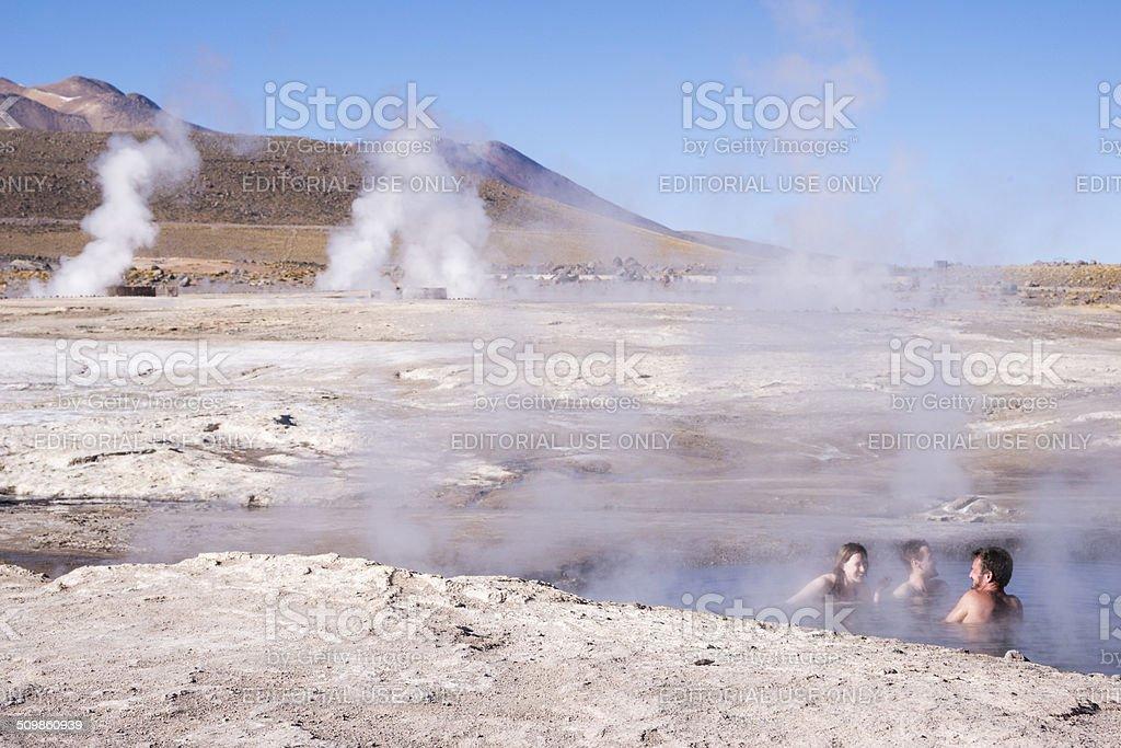 Three people soaking in hot springs stock photo
