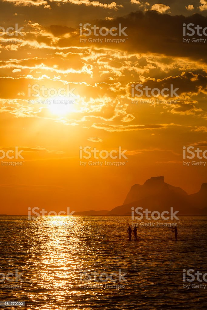 Three People Stand up Paddling at Sunset on Tranquil Sea stock photo